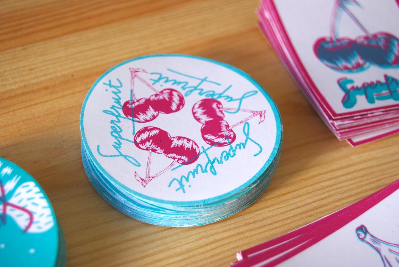 Zoom sur le sticker cerise bleu et rose en triangle avec une typographie Superfruit.