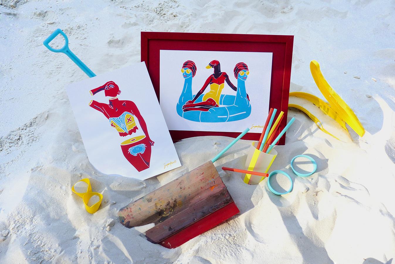Ensemble d'affichettes dans le sable sur la plage sous un soleil couchant, avec un pelle, des pailles, un cadre et une racle de sérigraphie.
