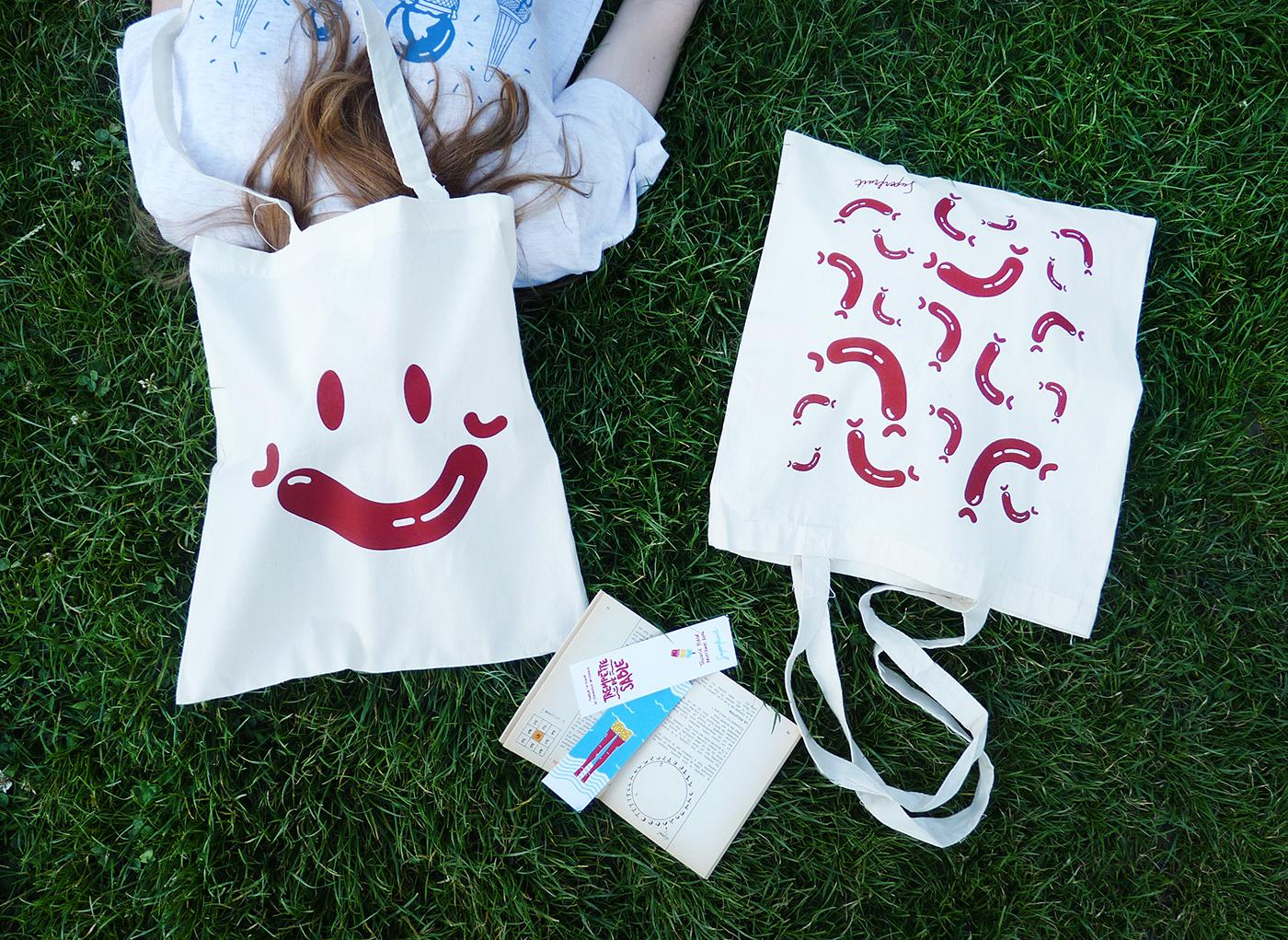 Tote bags recto verso avec all over de saucisse et smiley wurst posés dans l'herbe. Marques pages colorés posés dans un livre.
