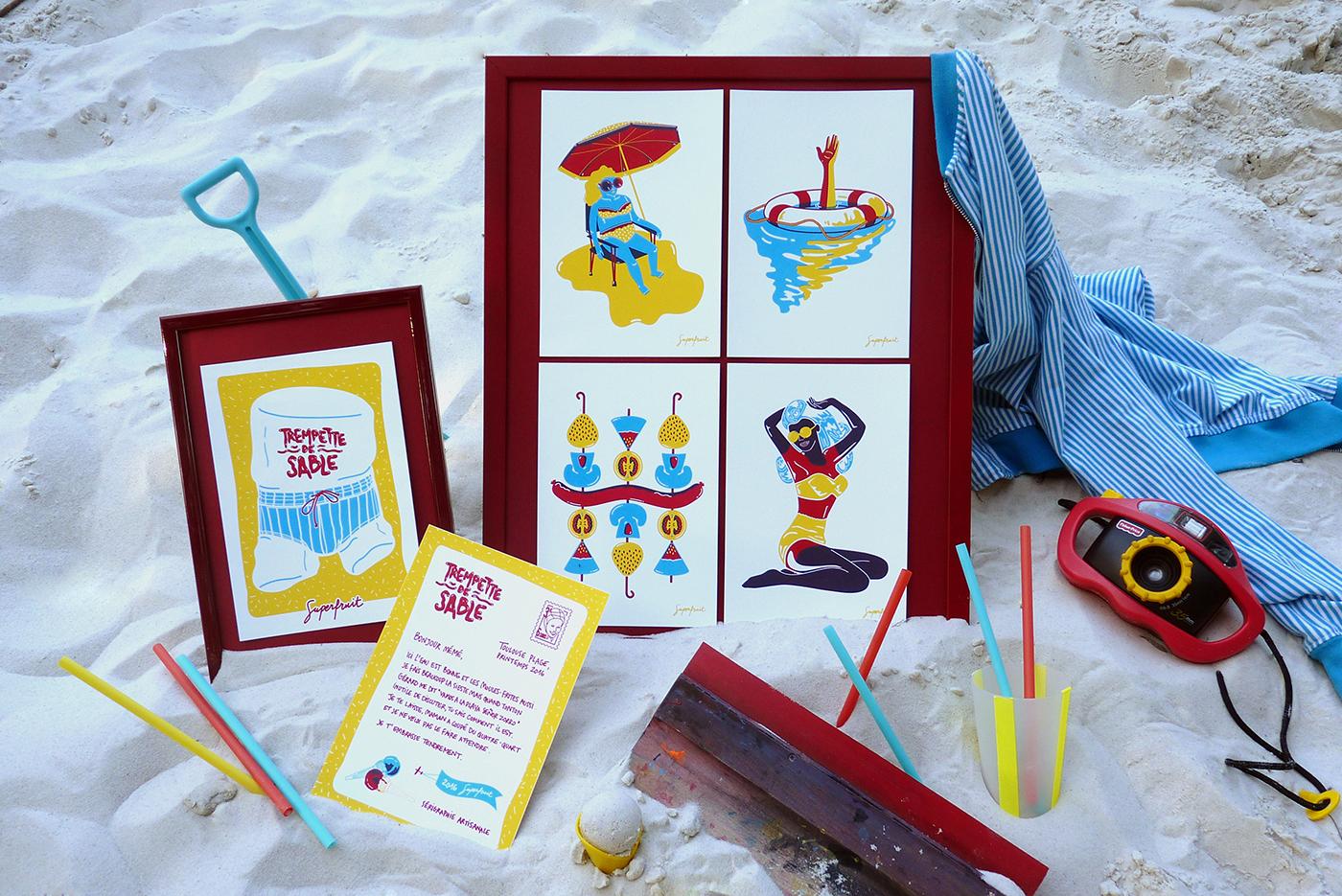 Ensemble du lot de cartes sérigraphiées dans le sable sur la plage, avec un pelle, des pailles, un cadre et une racle de sérigraphie.