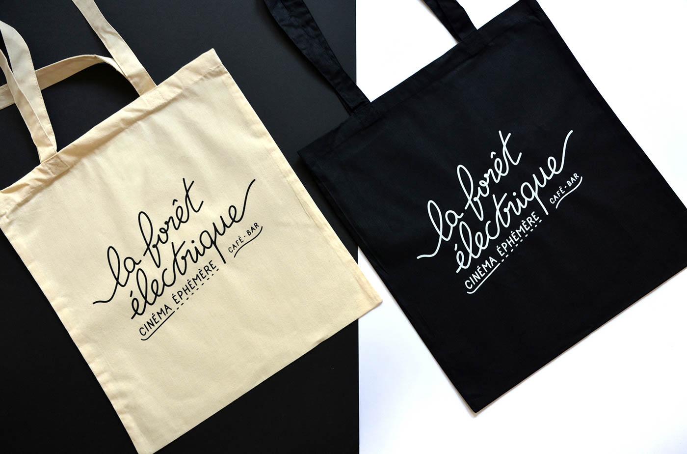 Photo des tote bags noir et couleur naturel avec la typographie imprimée en sérigraphie par Superfruit pour la Foret Electrique