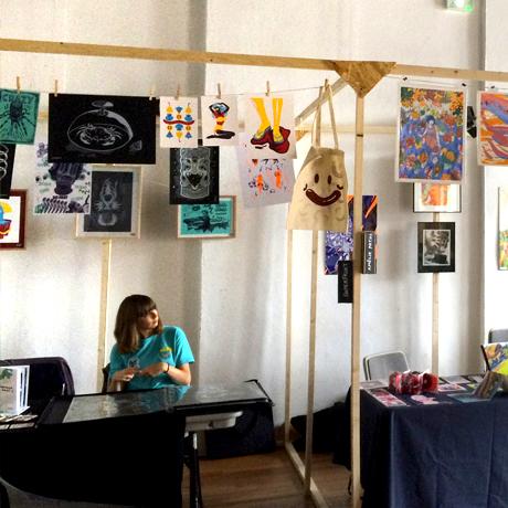 """Aperçu du stand Superfruit au Festival de micro édition """"L'Enfer"""" à Nancy, structure en bois et affiches sérigraphiées"""