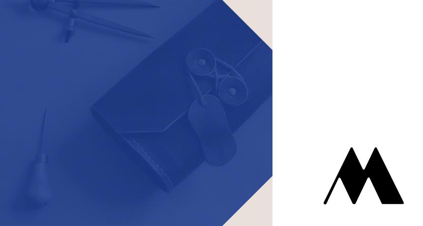 Lettre M du logo Ménétrier avec sac en cuir et outils artisanaux