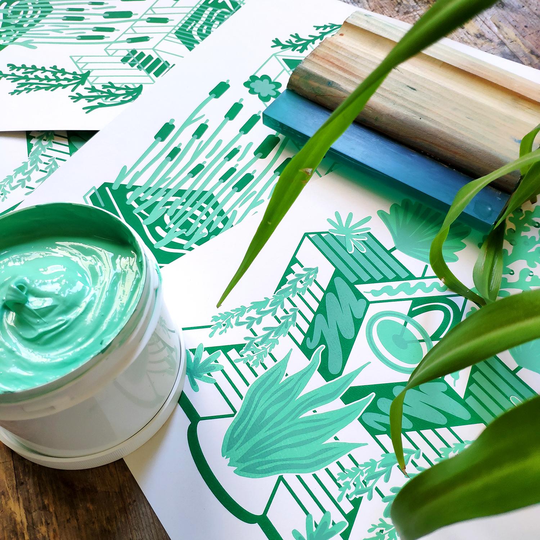 affiches sérigraphiées en vert disposées sur une table en bois accompagné d'une racle de sérigraphie, d'encre à l'eau et d'une plante.