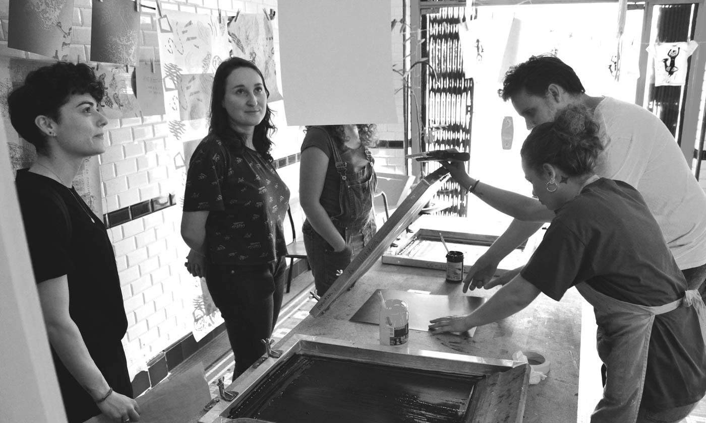 Groupe d'humain imprimant en sérigraphie dans une ancienne boucherie de Toulouse