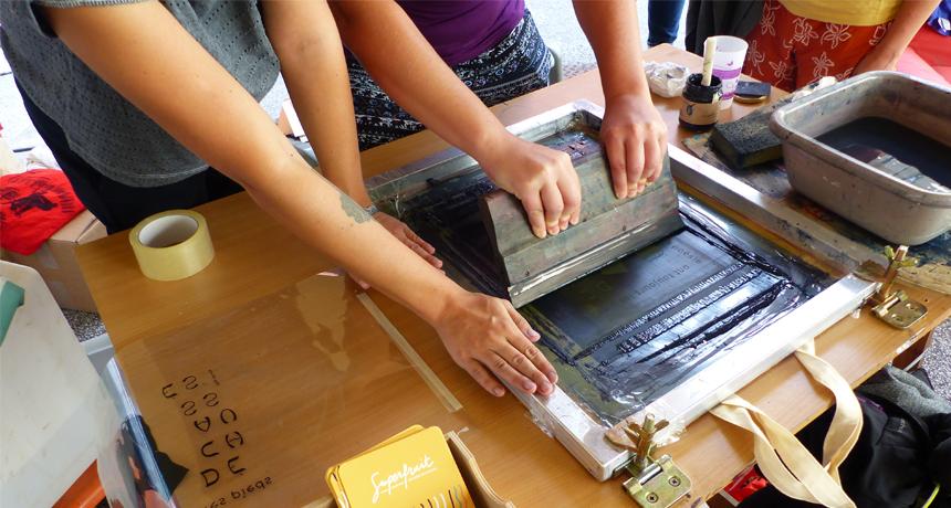 Gros plans sur des humains entrain d'imprimer en sérigraphie artisanale à la Cave Poésie (Toulouse)