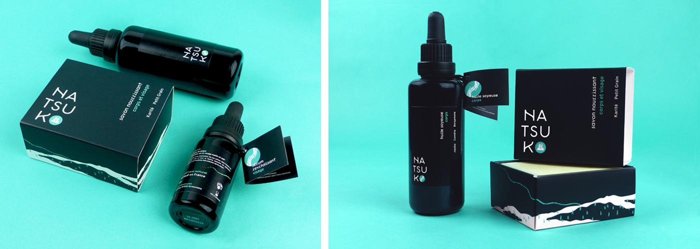 Ensemble photographique des produits de la gamme de soin Natsuko : savons et huiles dans leurs emballages noirs, épurés et hauts de gamme.